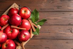 Fresh apples and cinnamon sticks on wooden table stock photography
