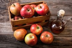 Fresh apples in crates and apple vinegar Royalty Free Stock Photos