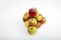 Fresh apples forming pyramid over white background Royalty Free Stock Images