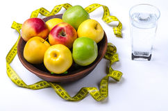 Fresh apples and a glass of water on a white background. A healthy diet, apples and a measuring tape Stock Photo