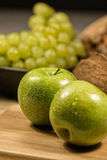 Fresh apples, grapes and coconut. Fresh apples in the composition of grapes and coconut. Deep bokeh Stock Images