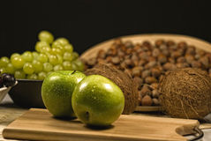Fresh apples, grapes, coconut and hazelnuts. Fresh apples in the composition of grapes, hazelnuts and coconut. Deep bokeh Stock Photo