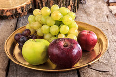 Fresh apples and grapes on golden plate over wooden background Royalty Free Stock Photos