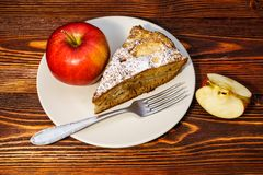 Fresh apples and a piece of apple pie sprinkled with powdered sugar on the background of a dark board. Fresh apples and a piece of apple pie sprinkled with stock images