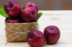 Fresh apples with water drop in a sugar palm leaf weave container Royalty Free Stock Photo