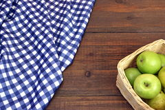 Fresh Apples In The Wicker Basket On Rustic Wood Table. Fresh Apples In The Wicker Basket On The Rustic Rough Brown Wood Table With Blue Checkered Tablecloth stock photos