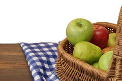 Fresh Apples In The Wicker Basket On Rustic Wood Table. Fresh Apples In The Wicker Basket On The Rustic Rough Brown Wood Table With Blue Checkered Tablecloth royalty free stock photo
