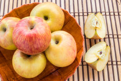 Fresh apples in wooden plate on wooden table background Stock Photography