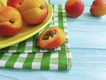 Fresh apricot on a blue wooden background dish, towel. Fresh apricot on a blue wooden backgroundn orange dish towel stock photos