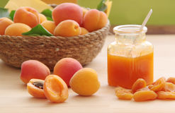 Fresh apricot, dried apricots and apricot jam. Fresh fruit in a wicker basket on background. Close up view. Royalty Free Stock Images
