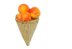 Fresh apricot kept in handwoven conical basket Stock Photos