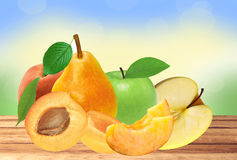 Fresh apricot, peach, apple and pear on wooden table over nature Stock Photography