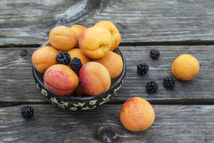 Fresh apricots with blackberry in ceramic bowl on Stock Image
