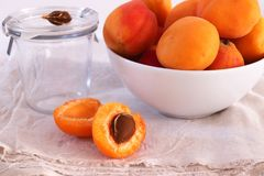 Fresh apricots in a bowl. One apricot just halved, on natural linen cloth and white background royalty free stock image