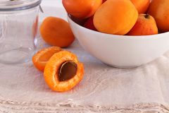 Fresh apricots in a bowl. One apricot just halved, on natural linen cloth and white background royalty free stock photo