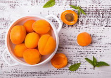 Fresh apricots in a bowl on the white colored table. Royalty Free Stock Photo