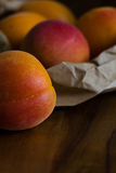 Fresh apricots in a brown paper bag on a wood background with copy space. Farteli variety, grown in Spain. Close up. Royalty Free Stock Photos