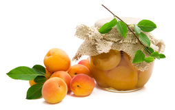 Fresh apricots with green leaves,jam in glass jar stock photo