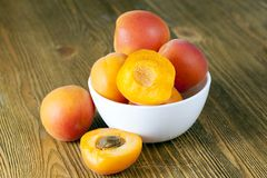Fresh apricots. Plates with fresh apricots, some of which are cut into half, a beautiful color of fruit Royalty Free Stock Photos