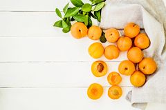 Free Fresh Apricots Scatter With Green Leaves On White Wooden Background With A Table Linen Top View Royalty Free Stock Photography - 120092007