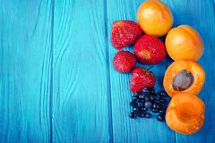 Fresh apricots, strawberries and blueberries  on wooden turquoise background. Royalty Free Stock Photo