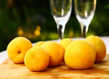 Fresh apricots on the summer background with wine glasses royalty free stock photo