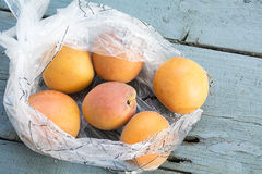 Fresh apricots in a transparent plastic bag on old blue-gray woo Stock Photos