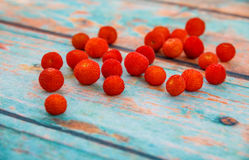 Fresh arbutus fruits. On  background imitating an old tree. photo with shallow depth of field Royalty Free Stock Image