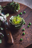 Fresh artichokes on a cutting board. Top view Royalty Free Stock Photos