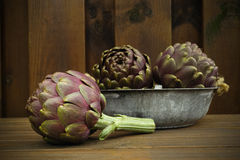 3 fresh artichokes green-purple flower head, on wooden backgroun Royalty Free Stock Photography
