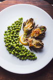 Fresh artichokes with parsley and young beans in a baking pan, parmesan in background. Top view Royalty Free Stock Image