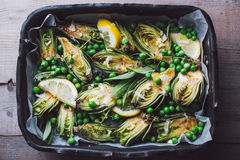 Fresh artichokes with parsley and young beans in a baking pan. Top view Stock Photography