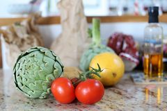 Fresh artichokes, potatoes, tomatoes and grapefruit in a kitchen mirroring in the counter Royalty Free Stock Photography