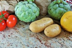 Fresh artichokes, potatoes, tomatoes in a kitchen mirroring in the counter Royalty Free Stock Photo