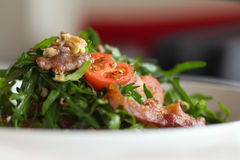 Fresh arugula salad. With cherry, nuts and bacon royalty free stock image