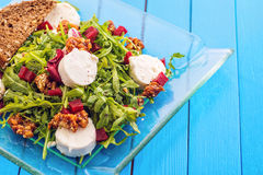 Fresh arugula salad with beetroot, goat cheese, bread slices and walnuts on glass plate on blue wooden background, product photogr Stock Images
