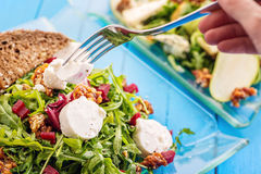 Fresh arugula salad with beetroot, goat cheese, bread slices and walnuts with metal fork in hand, product photography for restaura Royalty Free Stock Photo