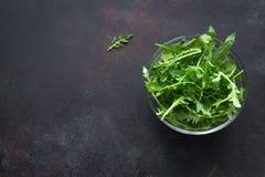 Fresh Arugula Salad. On dark background, copy space. Organic Arugula Leaves - healthy food salad ingredient royalty free stock image