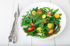 Fresh arugula salad with kumquat and tomato cherry on white wooden background. Top view. Healthy food. Diet. Royalty Free Stock Photos