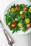 Fresh arugula salad with kumquat and tomato cherry on white wooden background. Top view. Healthy food. Diet. Stock Photos