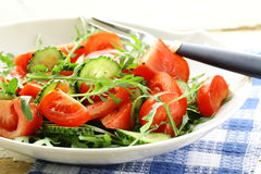Fresh arugula salad with tomatoes, cucumbers Stock Photo