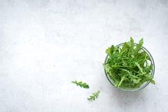 Fresh Arugula Salad. On white stone background, copy space. Organic Arugula Leaves - healthy food salad ingredient stock photo