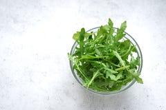 Fresh Arugula Salad. On white stone background, copy space. Organic Arugula Leaves - healthy food salad ingredient royalty free stock images