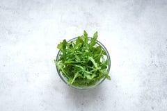 Fresh Arugula Salad. On white stone background, copy space. Organic Arugula Leaves - healthy food salad ingredient stock photos