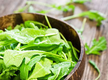 Fresh arugula salad. On wooden table royalty free stock photo