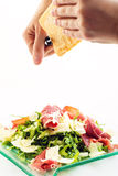 Fresh arugula vegetable salad with ham and cheese on glass plate  on white background and cooks hands shredding cheese, pr Stock Image