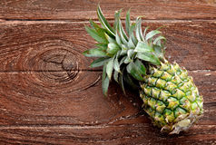 Fresh Asian small pineapple. On wooden plate in outdoor hard sunlight and dark shadow Stock Photography