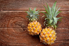 Fresh Asian small pineapple. On wooden plate in outdoor sunlight Royalty Free Stock Images