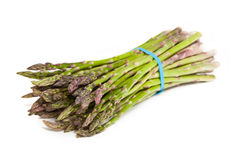 Fresh Asparagus. A bundle of fresh asparagus wrapped with an elastic band laying on a white background Royalty Free Stock Photography