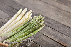 Fresh asparagus in basket. Fresh green and white asparagus in a basket on wooden background Stock Image